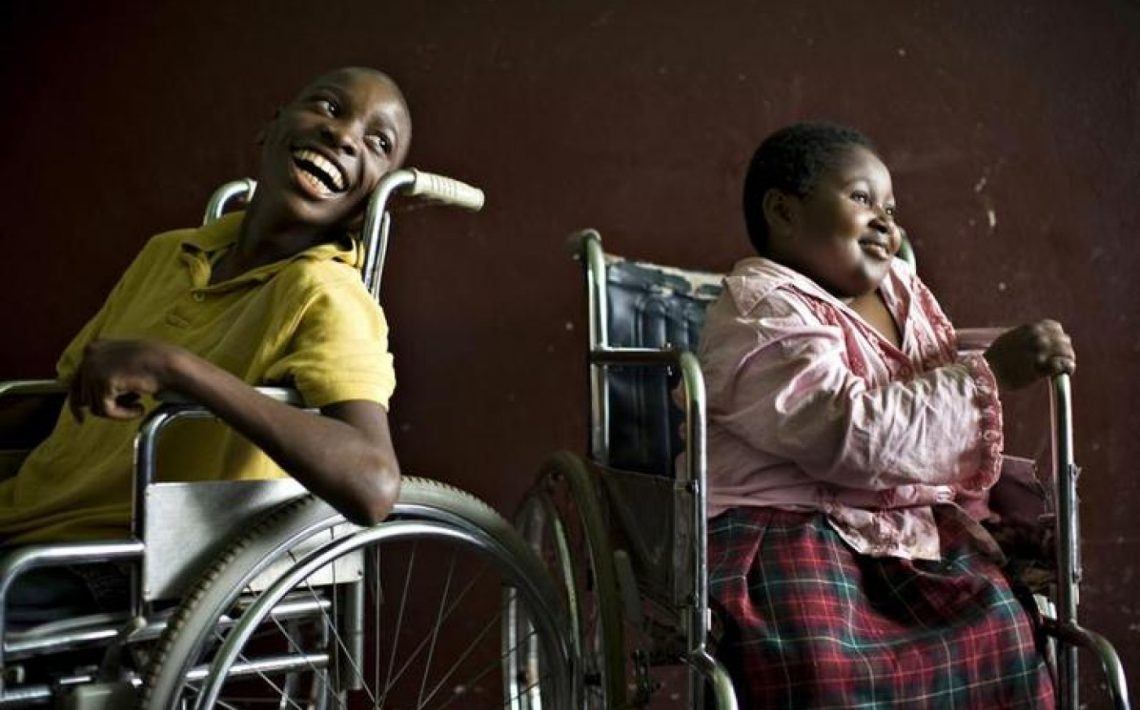 A boy and a girl both in wheelchairs looking on the right and smiling